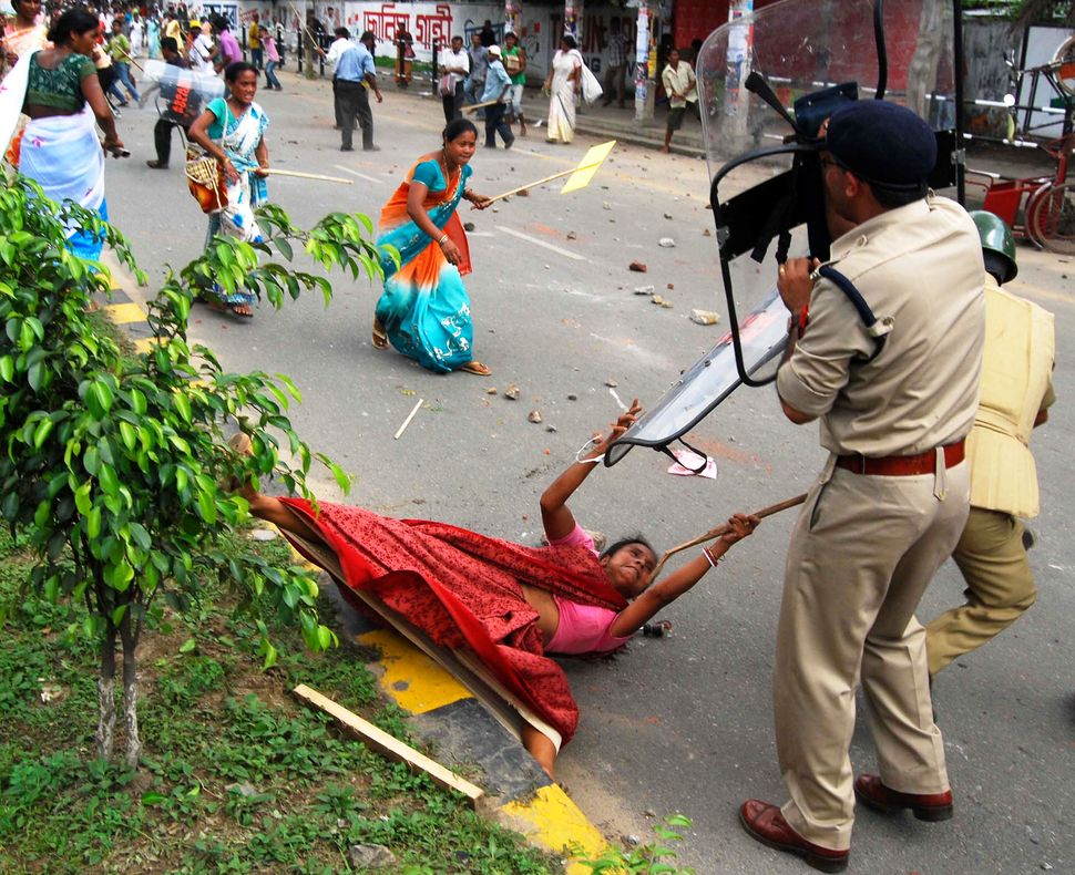 Indian policemen and activists from the Krishak Mukti Sangram Samiti (KMSS) clash during a demonstration in Guwahati on June