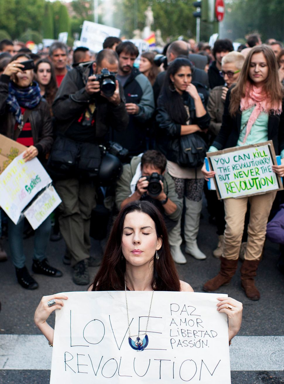 """A bare breast protester holds a placard reading """"Love unites us, we are all equal, we were born free and we will die free"""" du"""