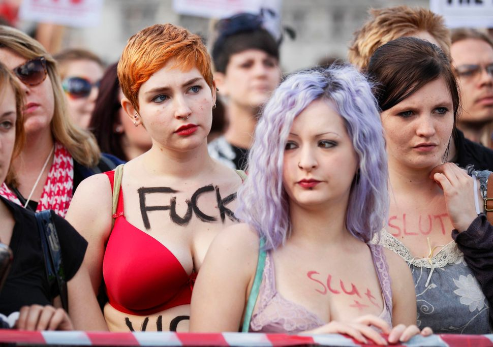 "Women bearing provocative words on their bodies take part in a ""slut walk"" in London on September 22, 2012 to protest against"