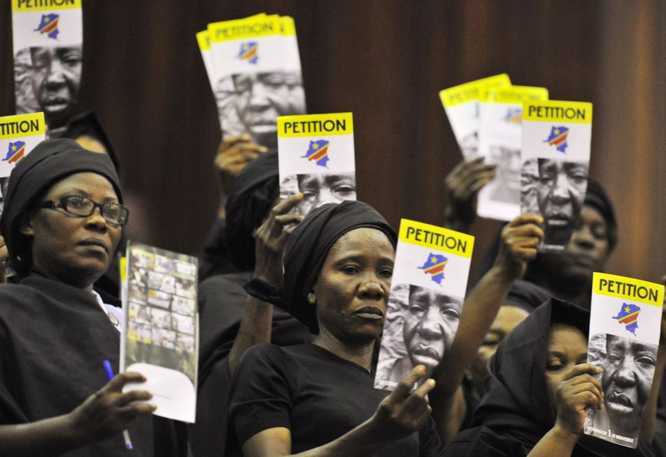 Female members of associations against violence towards women in the east of the Democratic Republic of Congo hold up leaflet
