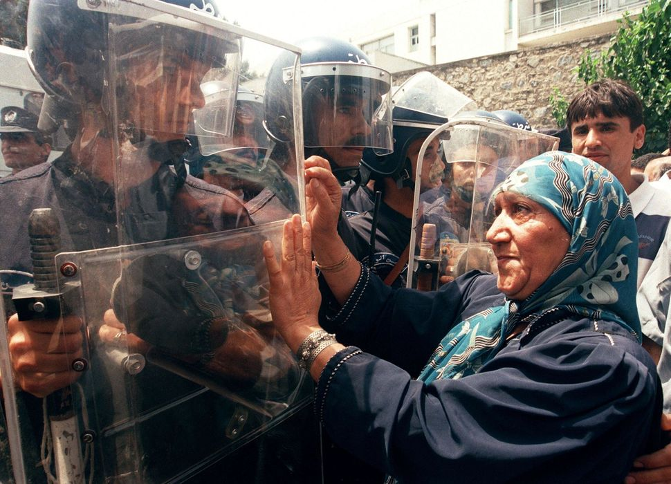 A woman gestures to riot policemen during a protest organized by the Rally for Culture and Democracy (RCD) in Algiers 02 July