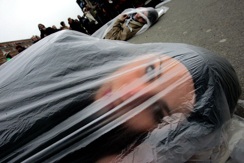 "A member of the ""Women in Black"", an international peace network, lays on the ground wrapped in a plastic bag, as a sign of p"