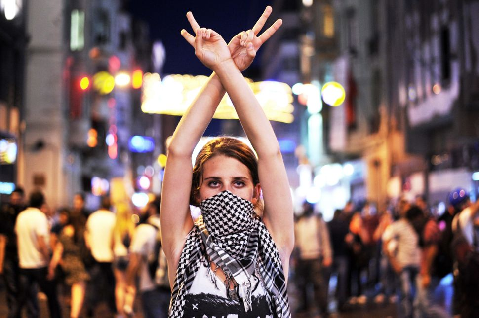 An anti government protester flashes a victory sign during the clashes between protesters and riot police on Taksim square in