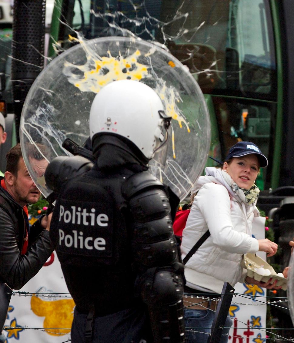 A woman throws eggs at riot police during a farmers demonstration in Brussels on Monday, Sept. 7, 2015. European dairy farmer