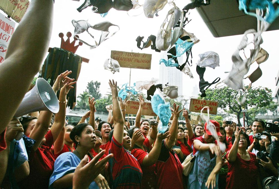 Women workers of Triumph International, the largest undergarment manufacturer in the Philippines, toss bras and panties in th