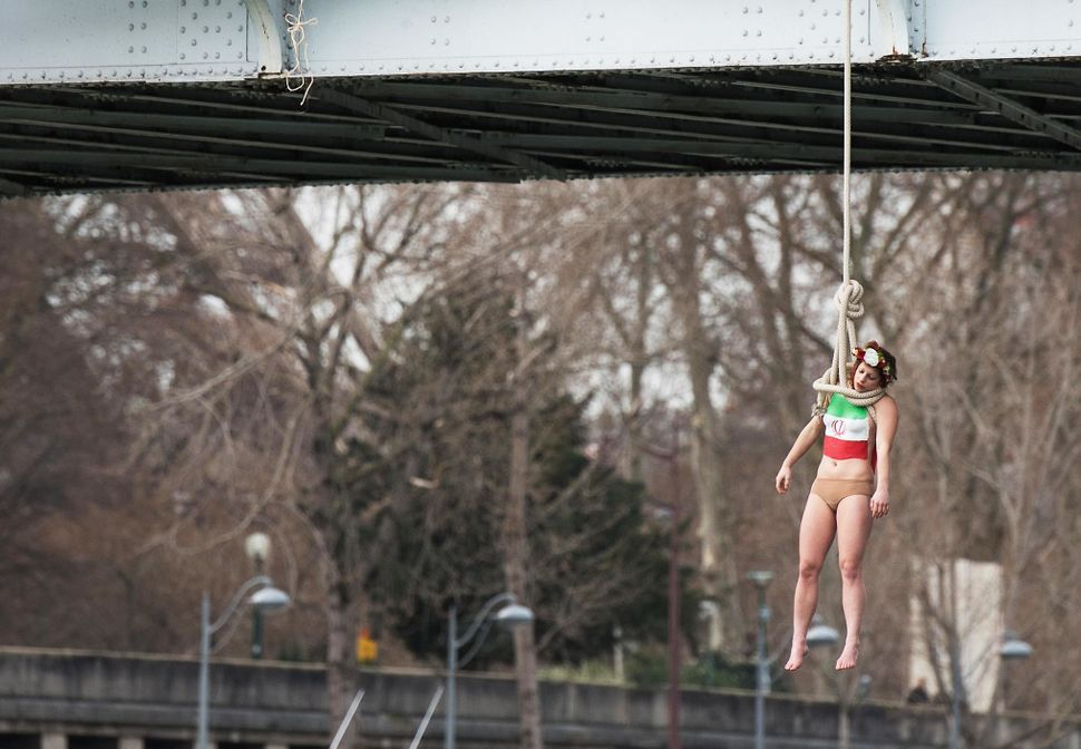 A Femen activist, Sarah Constantin, is hanged from a noose-like rope from a Paris bridge to call attention to the large numbe