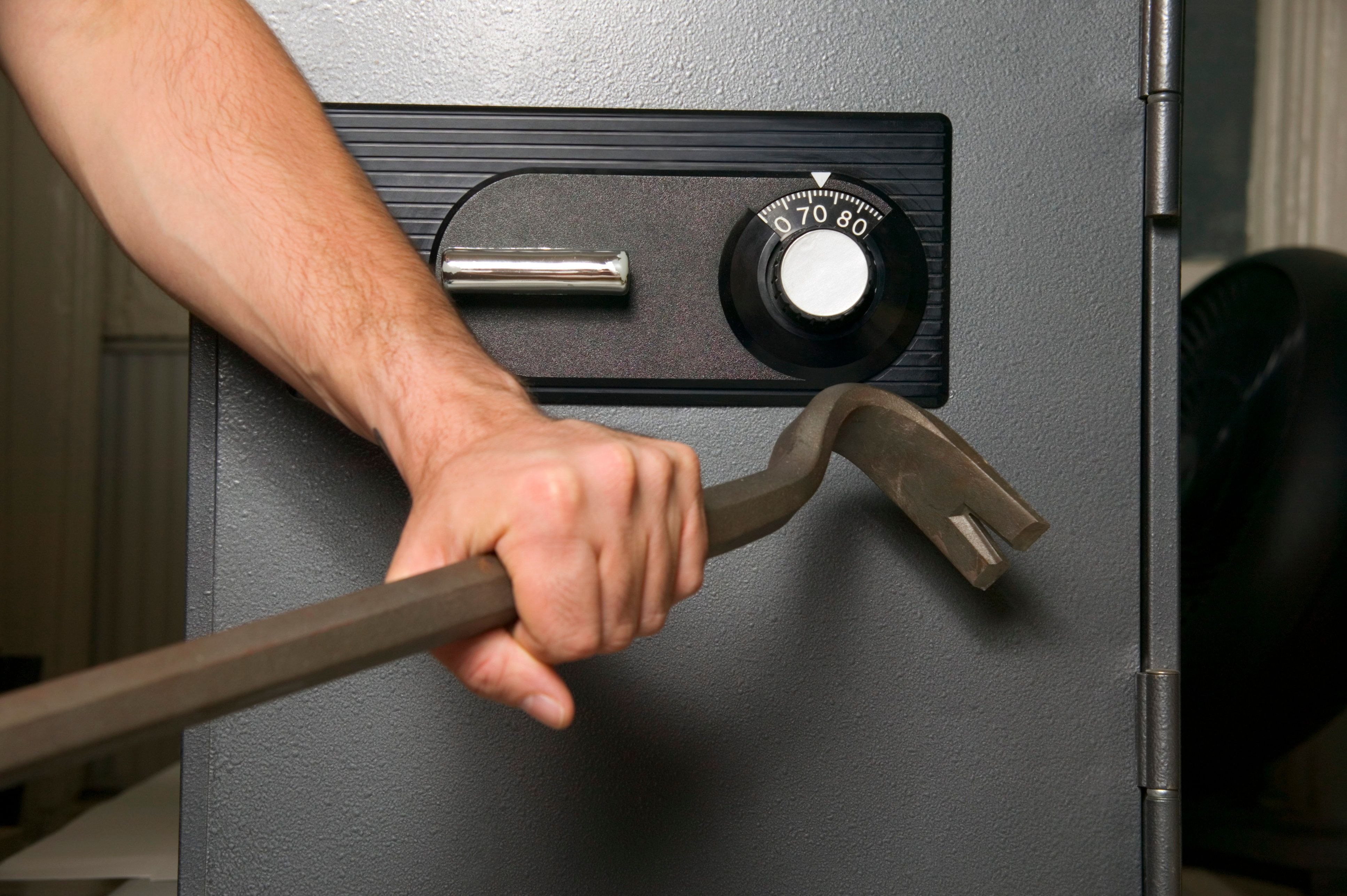 Hand prying safe with crowbar