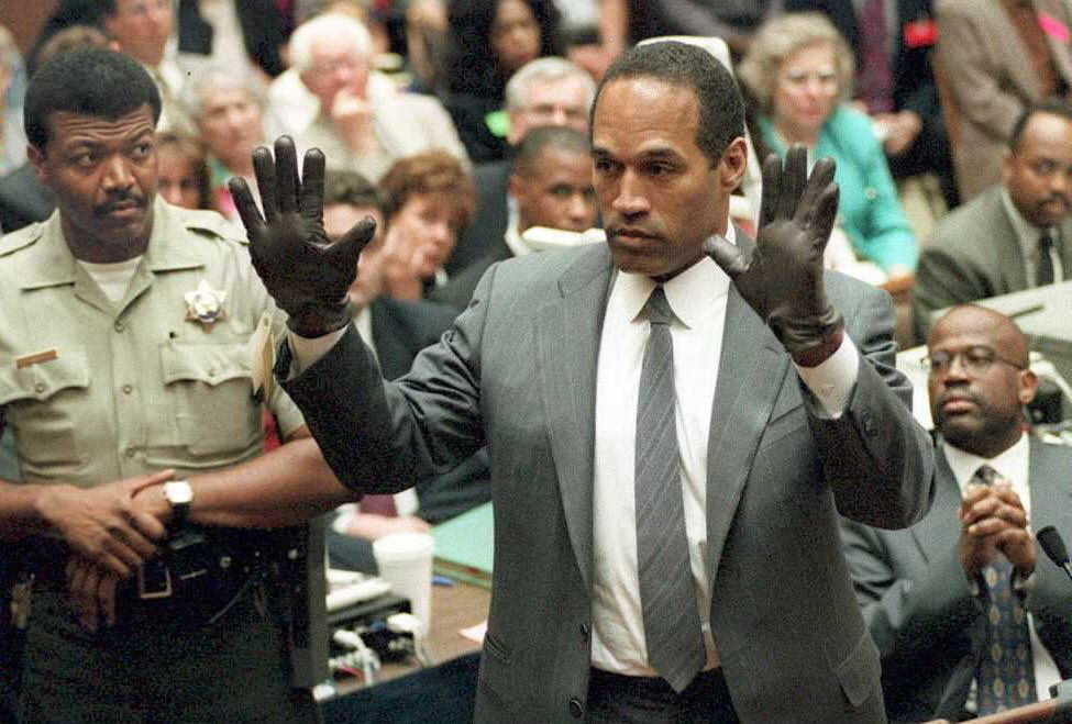 LOS ANGELES, CA - JUNE 21:  O.J. Simpson shows the jury a new pair of Aris extra-large gloves, similar to the gloves found at the Bundy and Rockingham crime scene 21 June during his double murder trial in Los Angeles. Depety Sheriff Roland Jex(L) and Prosector Christopher Darden(R) look on.   AFP PHOTO  (Photo credit should read POO/AFP/Getty Images)