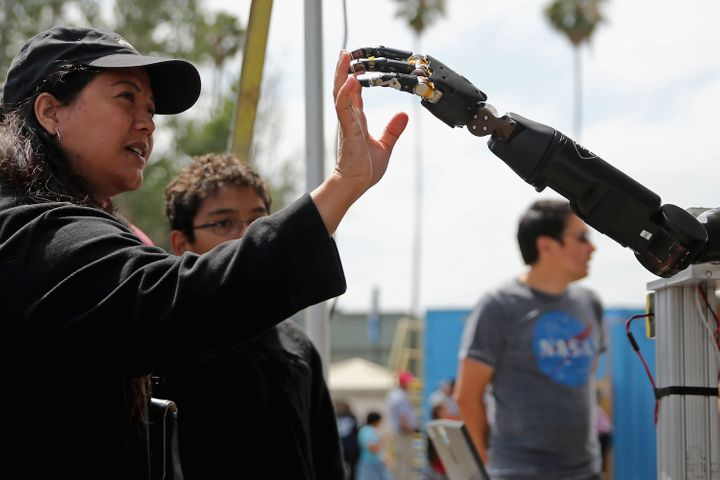 A woman reaches to touch a robotic arm developed by the Johns Hopkins University Applied Physics Laboratory, 2015.