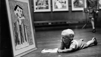 A toddler inspecting one of the paintings on display at the National Exhibition of Children's Art at the Royal Institute Galleries, London.