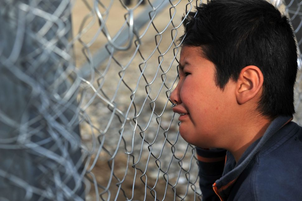 A boy cries while looking through a fence at the Greece-Macedonia border.