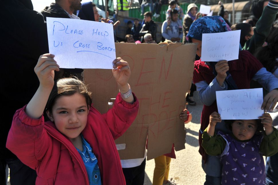 Children hold signs asking Macedonia to open the border.