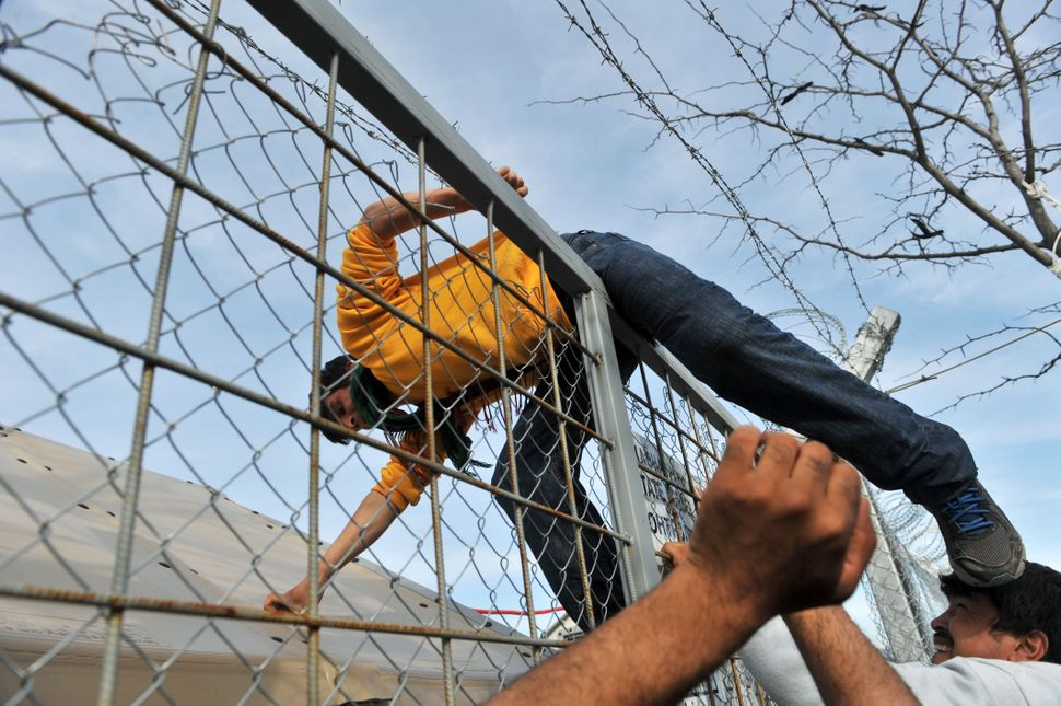 A man attempts to climb over a fence.