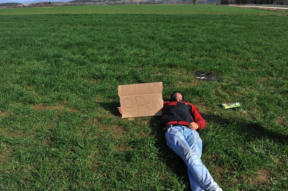 "A man lies on the ground with a placard reading ""Open."""