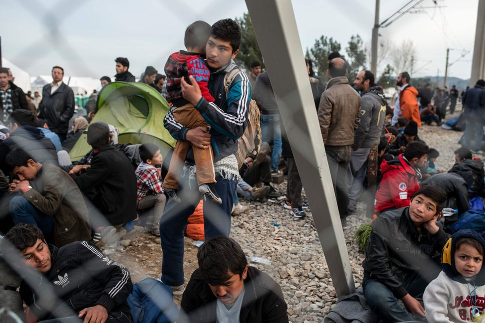 Men, women and children wait on the Greek side of the border. This photo was taken from the Macedonian side.