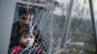 A photo taken from the Macedonian side of the border shows a man sitting with a young boy as migrants from Afghanistan gather behind a fence at the Greek-Macedonian border, near Gevgelija, on February 22, 2016, and protest against Macedonia's refusal to allow Afghans to pass the border. Greece said on February 22 that it was taking action to persuade Macedonia to take in Afghan migrants as thousands remained stranded at the border and the main port in Athens. About 5,000 refugees and migrants are stuck at the border with Macedonia after the neighbouring non-EU state on February 21 refused to allow passage to Afghans, police said. / AFP / Robert ATANASOVSKI        (Photo credit should read ROBERT ATANASOVSKI/AFP/Getty Images)