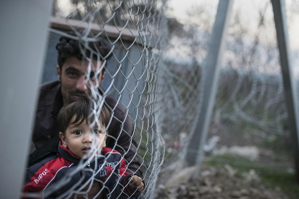 A man and a boy on the Greek side of the border look through a fence into Macedonia, which closed its borders to Af