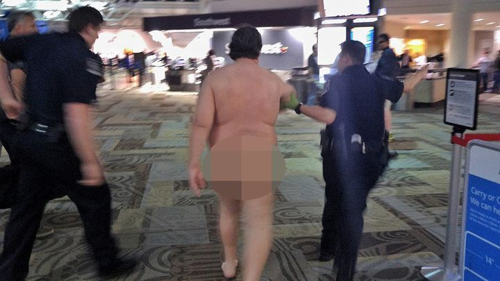 The eye-catching travelerwas led away by officers inside theairport.