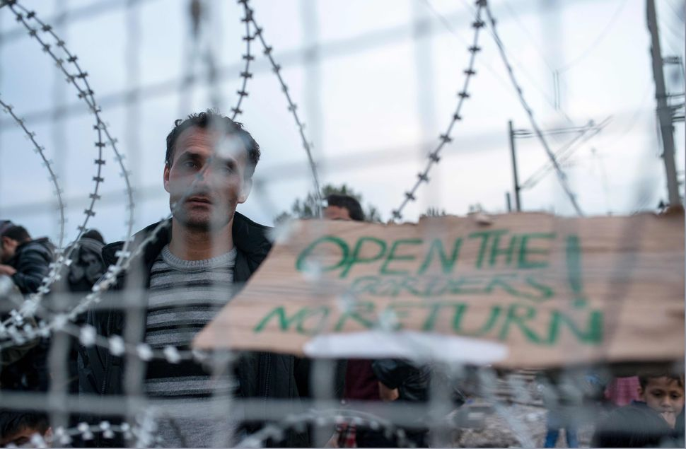 "People wait outside the Greece-Macedonia border. The sign reads, ""Open the borders. No return."""