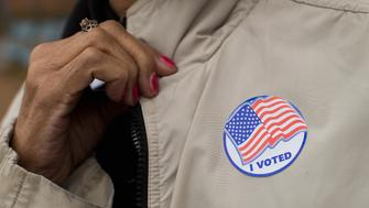 FERGUSON, MO - NOVEMBER 04: A voter shows off her 'I Voted' sticker as she leaves a polling place on November 4, 2014 in Ferguson, Missouri.  In last Aprils election only 1,484 of Ferguson's 12,096 registered voters cast ballots. Community leaders are hoping for a much higher turnout for this election. Following riots sparked by the August 9 shooting death of Michael Brown by Darren Wilson, a Ferguson police officer, residents of this majority black community on the outskirts of St. Louis have been forced to re-examine race relations in the region and take a more active role in the region's politics. Two-thirds of Fergusons population is African American yet five of its six city council members are white, as is its mayor, six of seven school board members and 50 of its 53 police officers.  (Photo by Scott Olson/Getty Images)