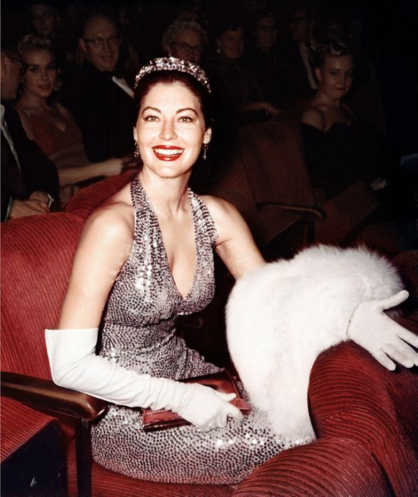 Actress Ava Gardner wears a tiara and a evening gown as she sits in her seat in the audience of the Academy Awards ceremony w