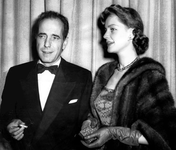 Humphrey Bogart and his film star wife Lauren Bacall pause for a smoke as they arrive at the theater for Academy Awards cerem