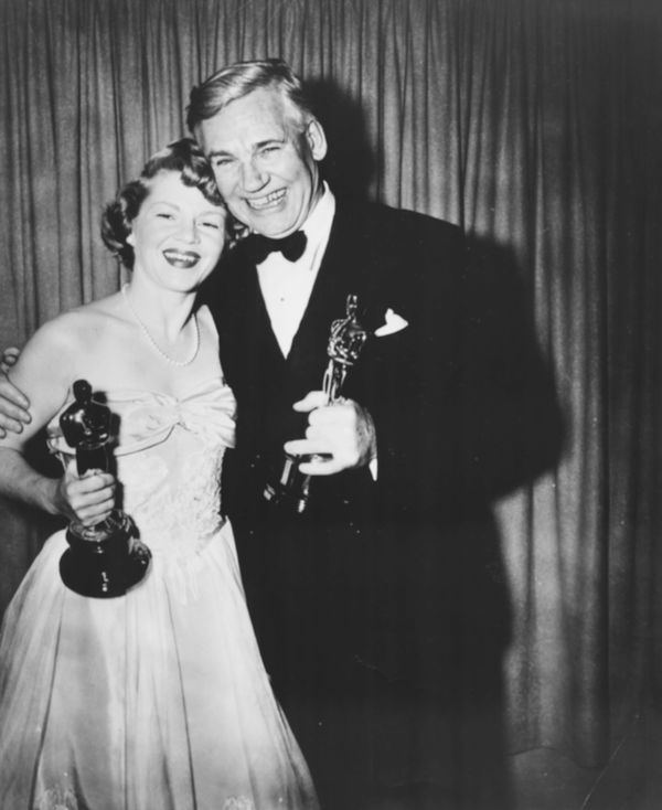 "Actress Claire Trevor holding her Best Supporting Actress Oscar for the film ""Key Largo"" with Walter Huston holding his"