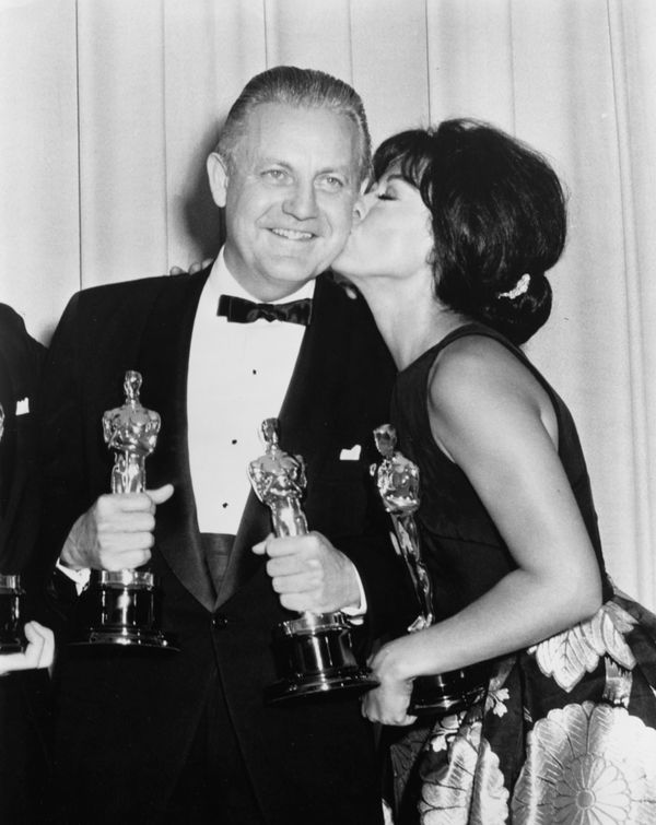 "Actress Rita Moreno kissing the cheek of director Robert Wise, both Oscar winners for their film ""West Side Story,"" at the 39"