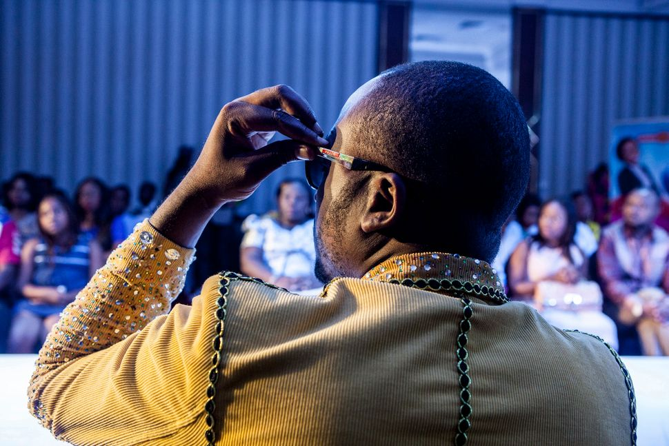 """Fashion designer Louison Mbeya watching the fashion show. The Democratic Republic of the Congo is known for its war, rebels"