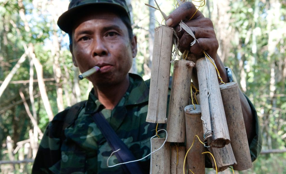 A soldier from the Karen National Liberation Army, one of Myanmar's armed ethnic groups, holds up a collection of homema