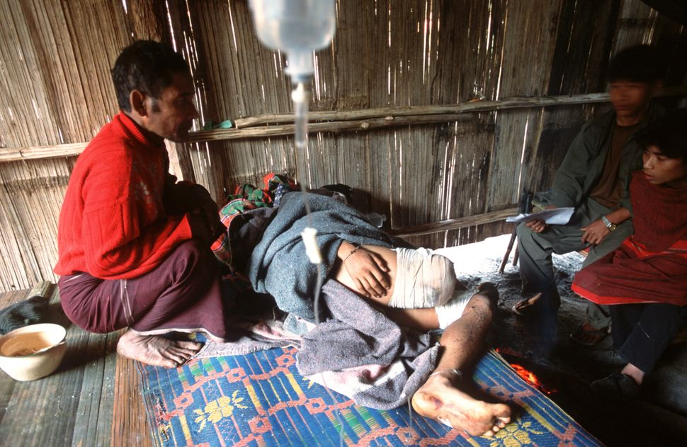 In this January 2004 photo, Cha Ka Luu Moo, a 17-year-old boy, is treated in a field hospital in Karen state after losing his