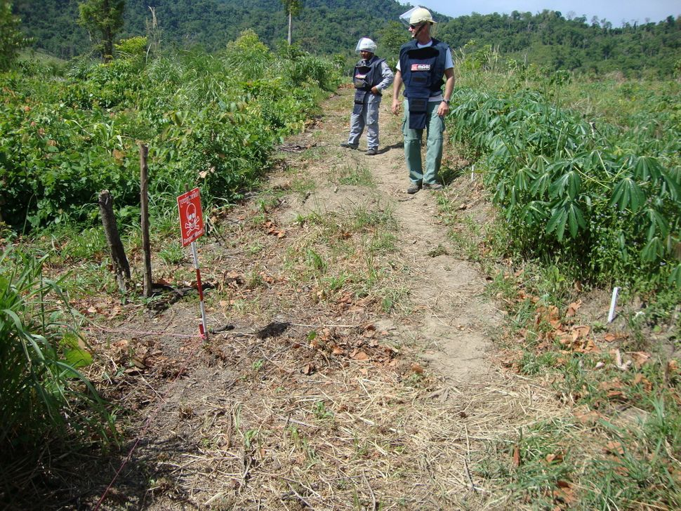 Detective Tony Langer, right, carrying out mine clearance in Battambang, Cambodia.