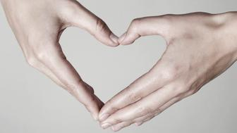 Close-up of hands forming a heart shape