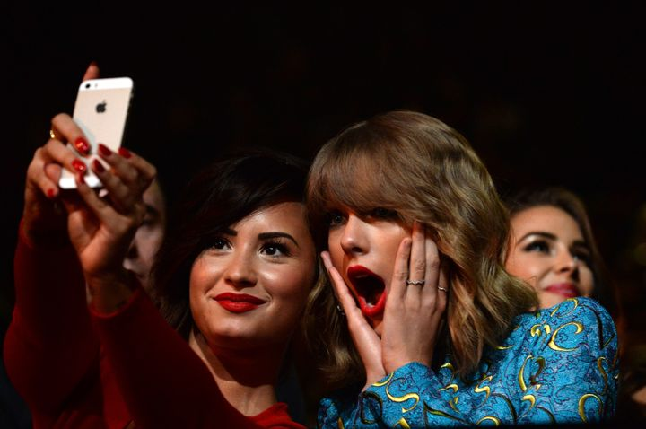 Recording artists Demi Lovato (L) and Taylor Swift take a selfie at the 2014 MTV Video Music Awards at The Forum on August 24