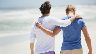 Rear view of two men walking with their arms around each other