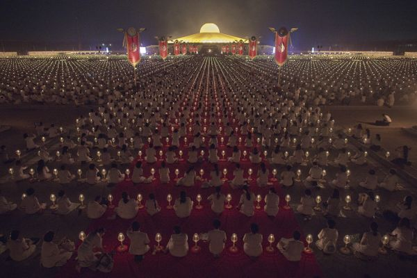 As night falls, hundreds of candles light up around the temple.