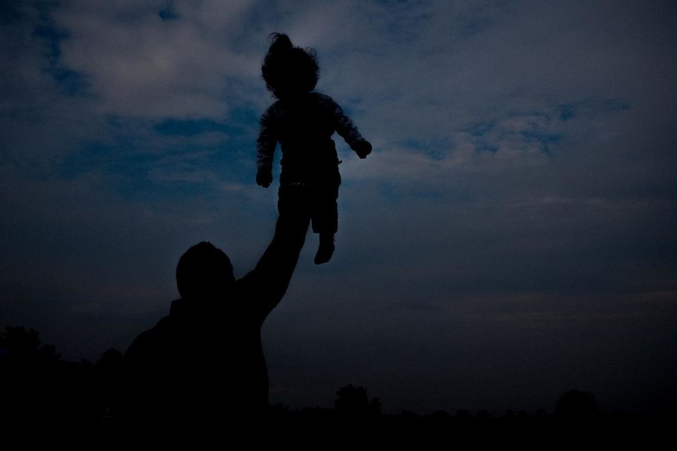 Holding her up towards the sky, a father plays with his daughter at a transit center for refugees and migrants in Sid, Serbia