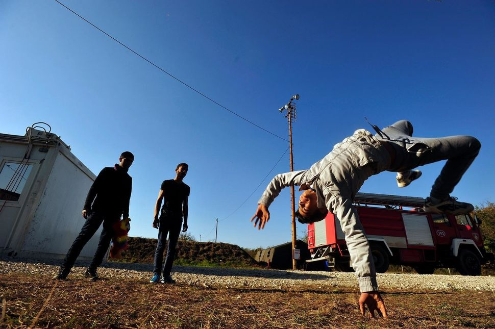 Teenagers play in the sun at a reception center staffed by volunteers, interpreters and humanitarian aid agenciesin Opa