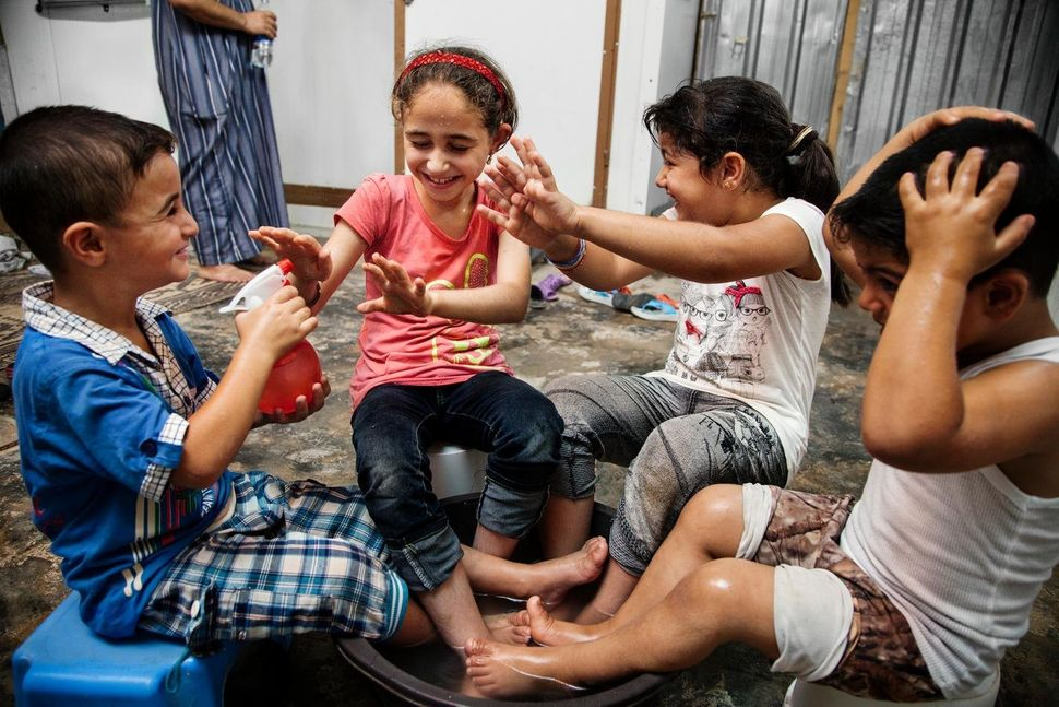 Mohammed, 5, from Syria, sprays water on his sister and cousins in Jordan's Zaatari refugee camp. The camp provides som
