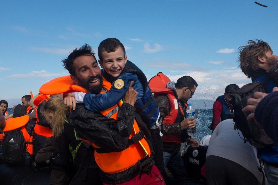 Syrian volunteer Kinan Kadouni, 26, carries a young Syrian boy moments after a boat landed on the coast of Lesbos,