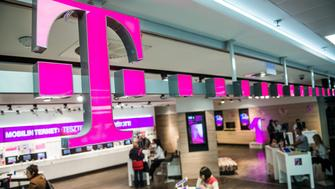 Customers browse mobile phone handsets as a sign sits above the entrance to a T-Mobile store, operated by Magyar Telekom Nyrt., in Budapest, Hungary, on Monday, Nov. 2, 2015. Magyar Telekom will announce third-quarter earnings on Wednesday. Photographer: Akos Stiller/Bloomberg via Getty Images