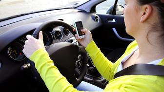 Automobile driver. France. Texting on a mobile phone