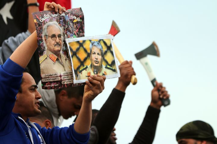 At left, a Libyan man holds a poster of General Khalifa Haftar, one of the UAE's top allies in Libya.