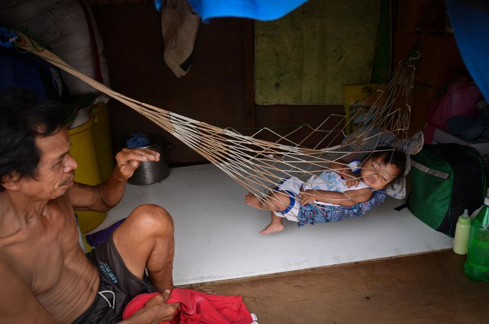 A man puts a baby to sleep in a hammock in Tacloban, Leyte, Philippines.