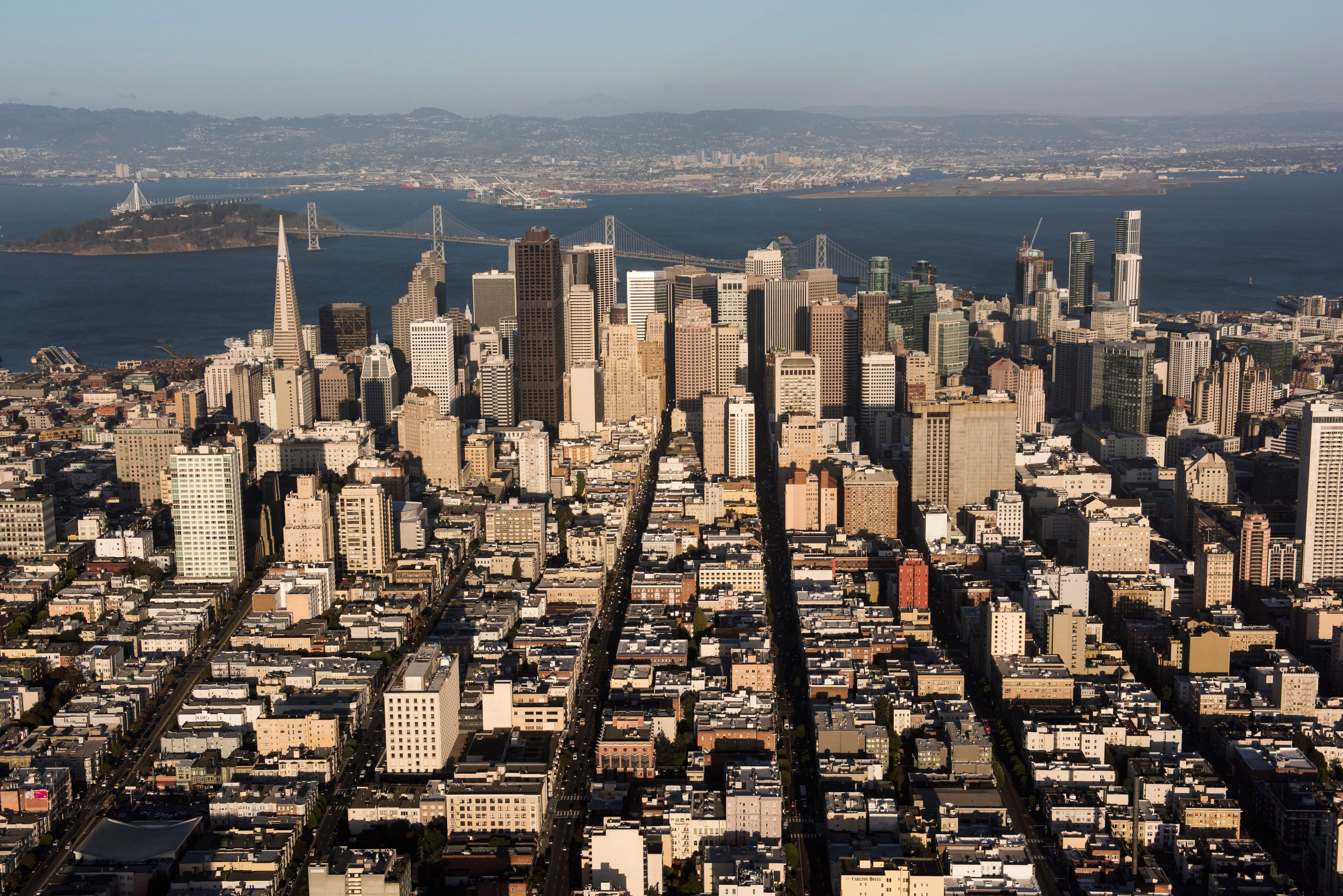 The Transamerica Pyramid building, left, stands in the skyline of downtown as the San Francisco-Oakland Bay Bridge crosses over Treasure Island in this aerial photograph taken above San Francisco, California, U.S., on Monday, Oct. 5, 2015. With tech workers flooding San Francisco, one-bedroom apartment rents have climbed to $3,500 a month, more than in any other U.S. city. Photographer: David Paul Morris/Bloomberg via Getty Images