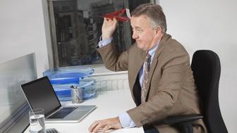Side view of middle-aged businessman throwing paper airplane in office