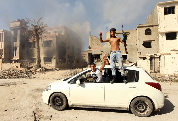 Fighters loyal to Libya's internationally recognized government celebrate as they come close to seizing the center of the eas