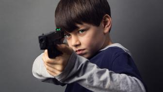 A young boy looking at the camera pointing a Handgun