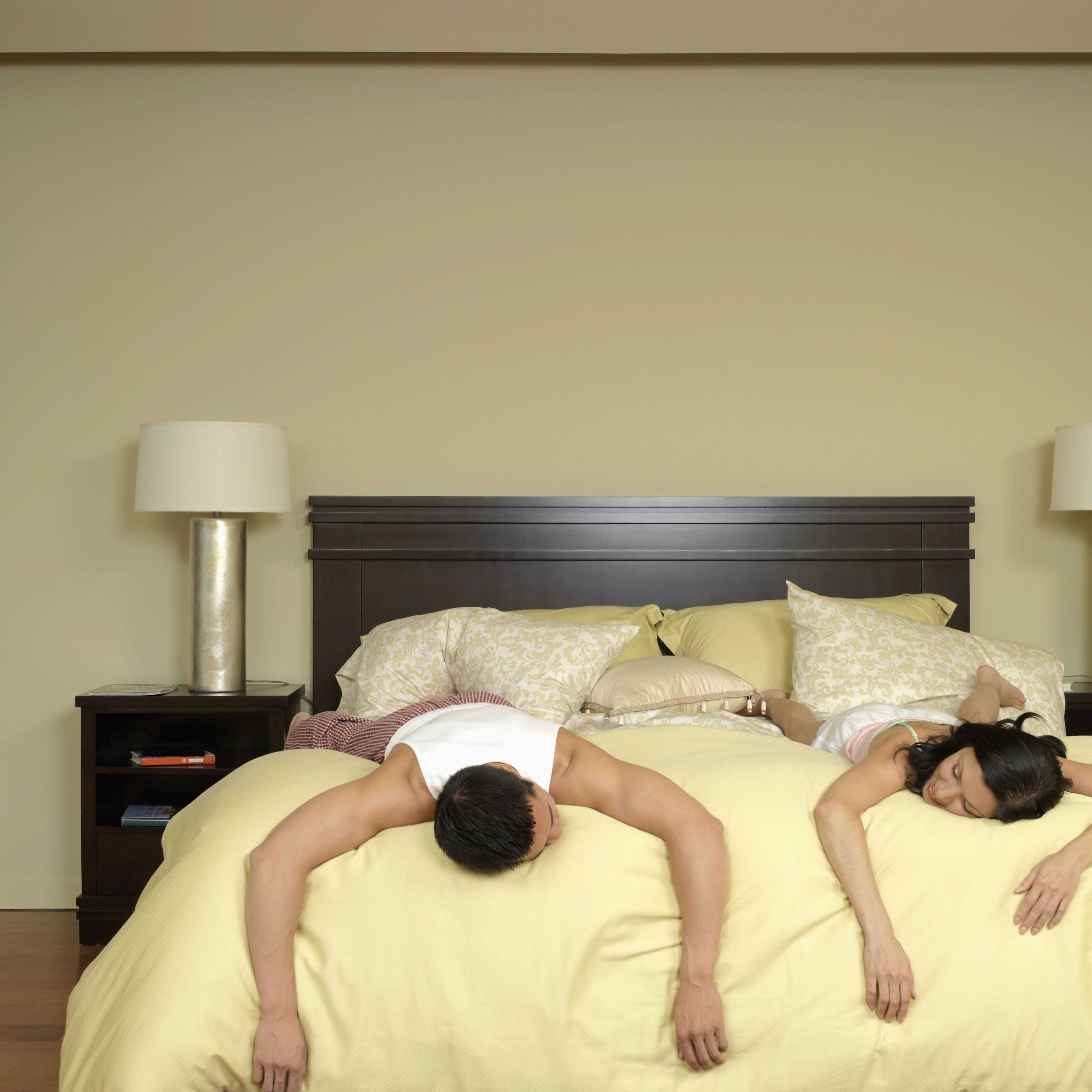 Asian couple laying on bed