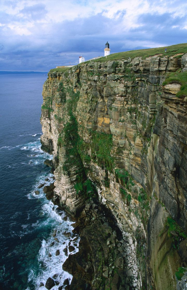 Dunnet Head lighthouse on a cliff overlooking Pentland Firth.